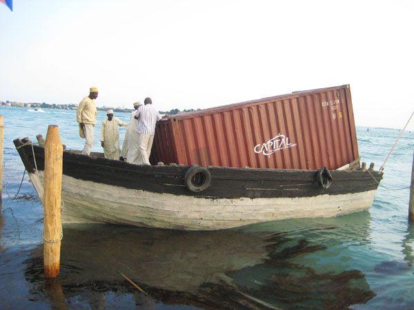 Einzelner Frachtcontainer auf einem kleinen Ruderboot